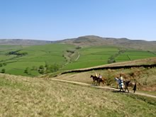 Horseriding group enjoying the Pennine Bridleway with the Derbyshire hills in the distance.